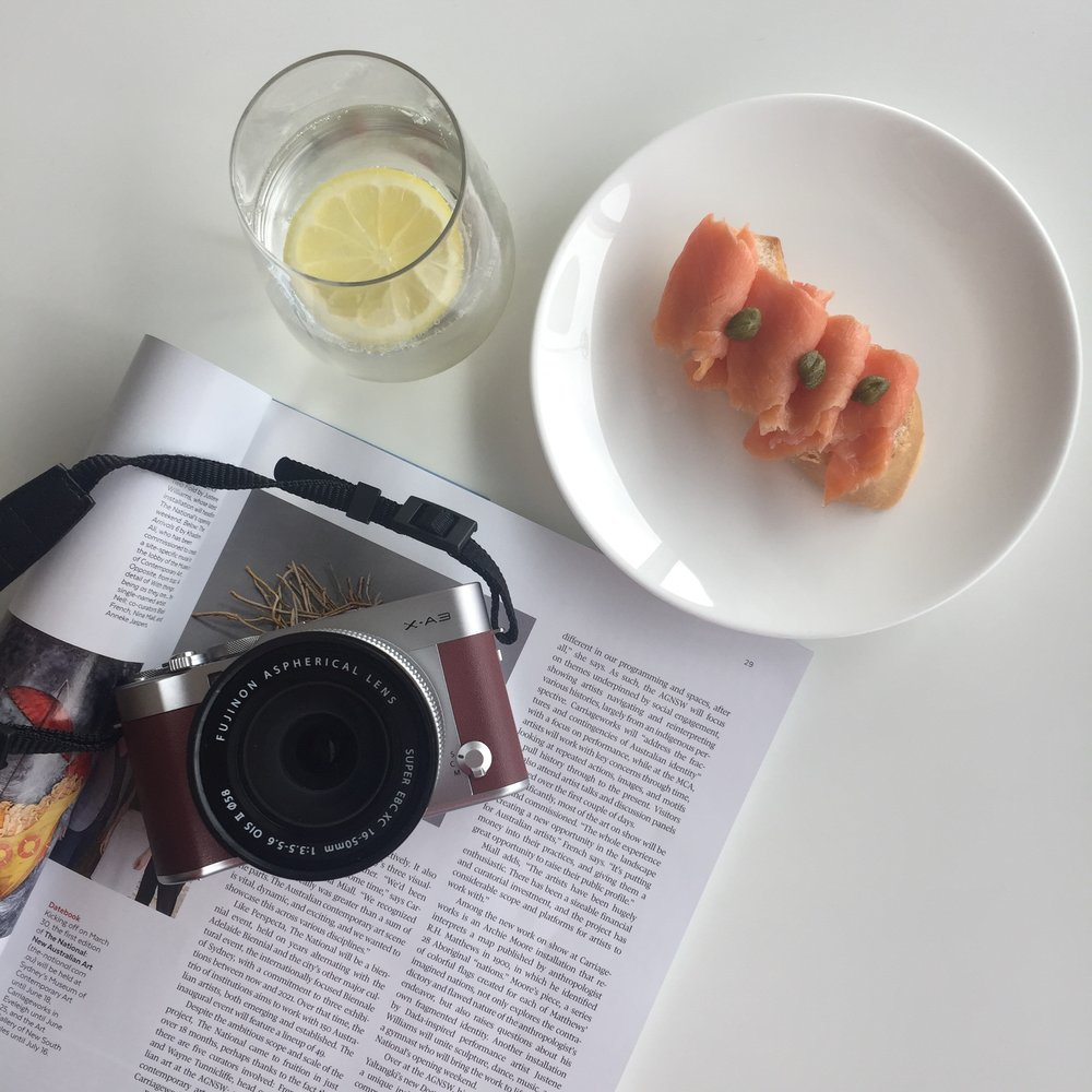 Camera on top of a magazine beside a drink and sandwich