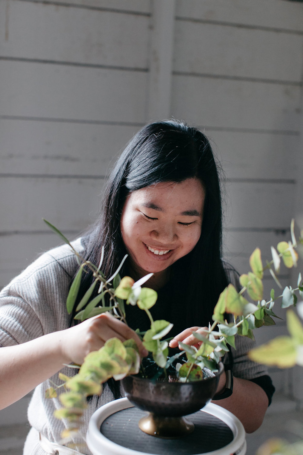 Girl smiling while arranging flowers