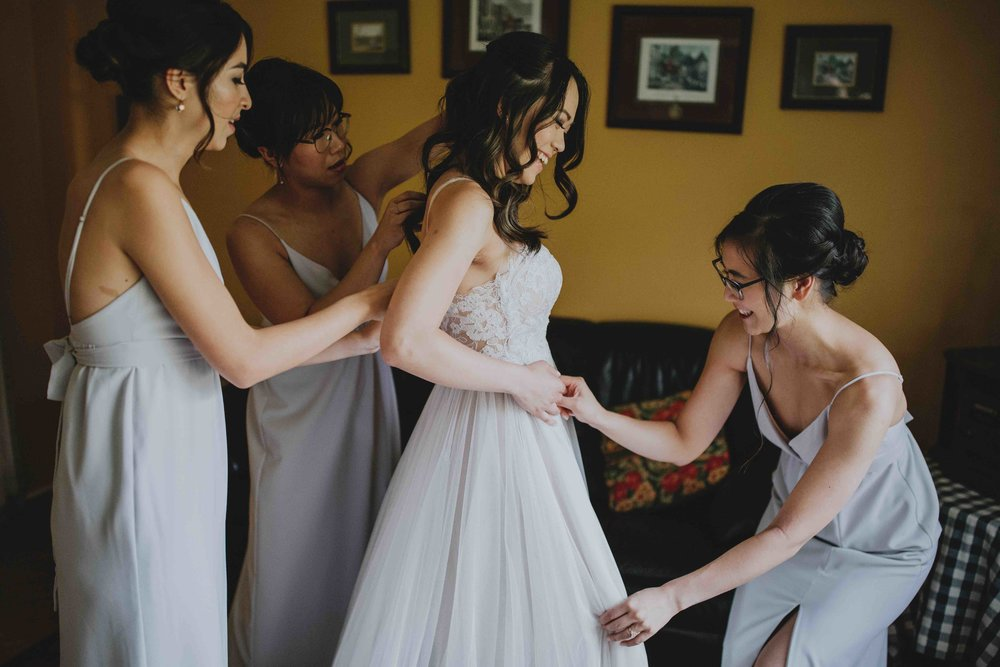 bridesmaids-helping-bride-fix-her-dress