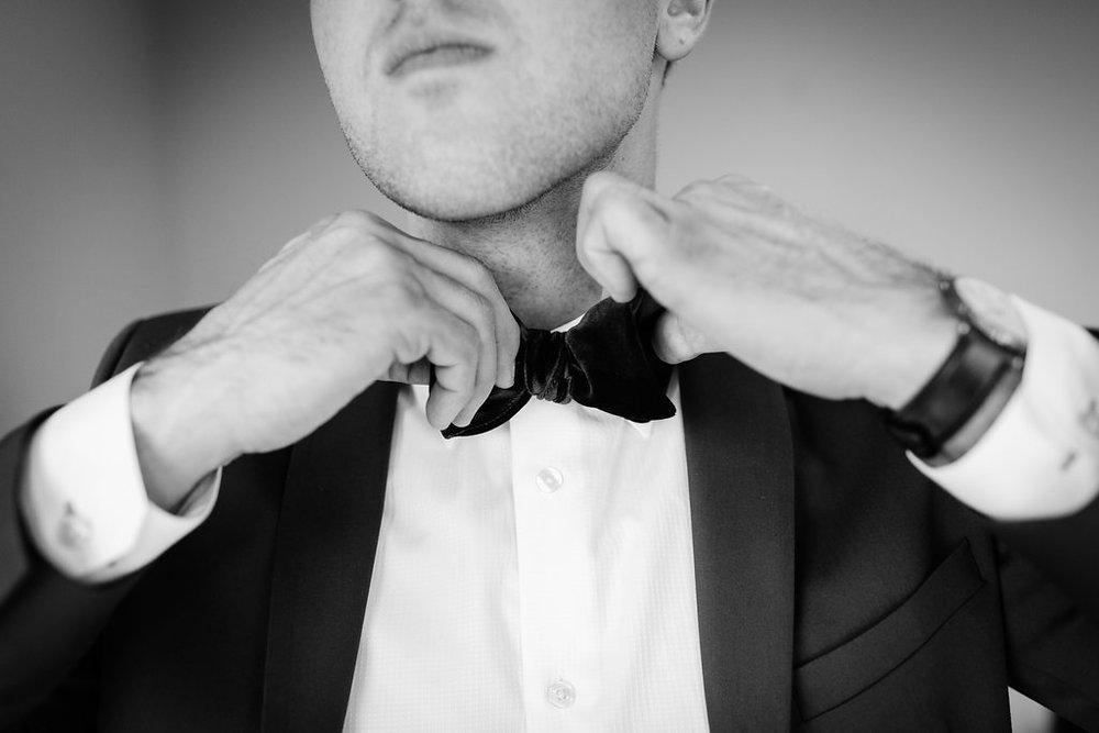 Groom-fixing-his-bow-tie
