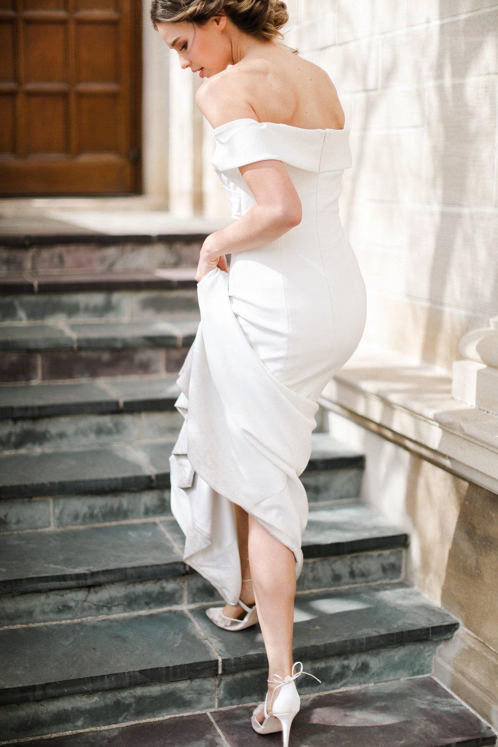 bride-walking-up-the-stairs-holding-gown