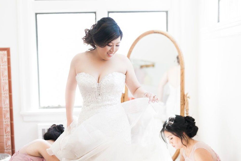 Bride-and-bridesmaids-fixing-wedding-dress