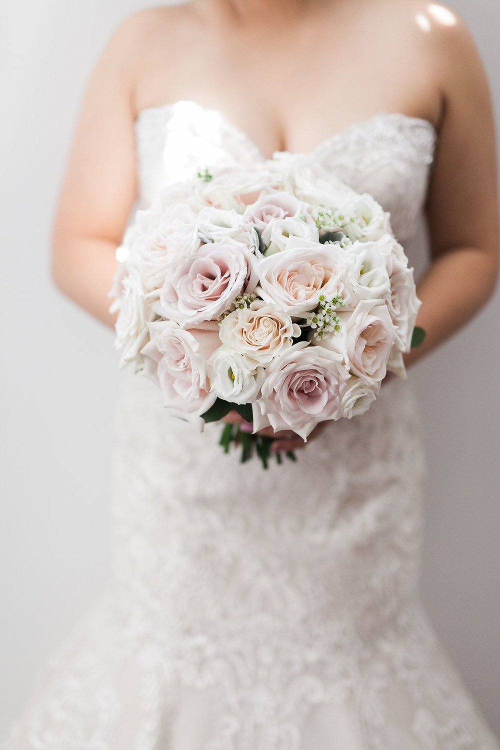 Bride-holding-cream-and-pink-circular-bouquet