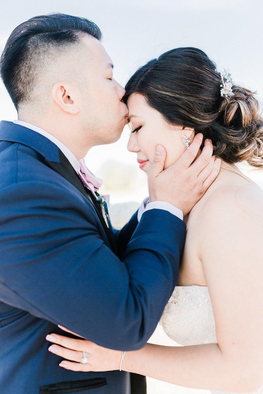 Groom-kisses-bride-on-forehead