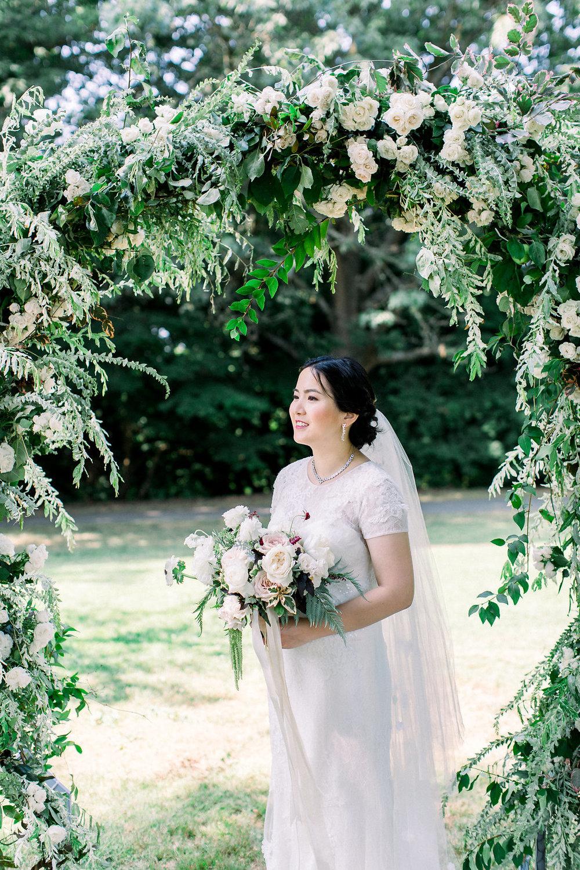 Bride-with-bouquet-under-floral-arch