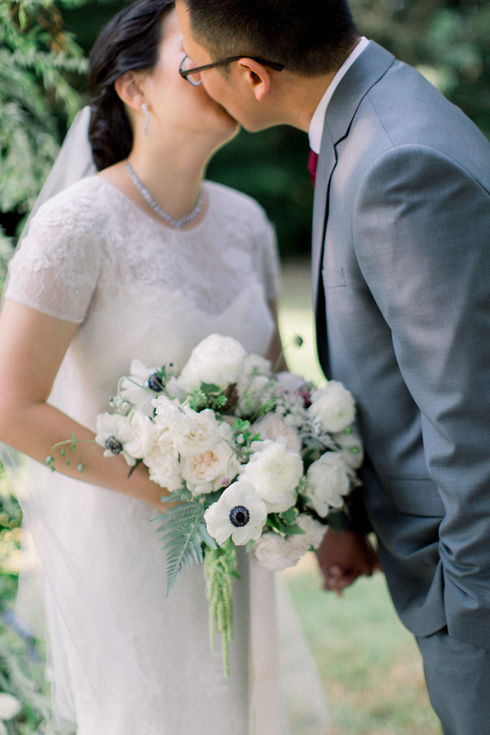 Bride-and-groom-kiss-under-floral-arch