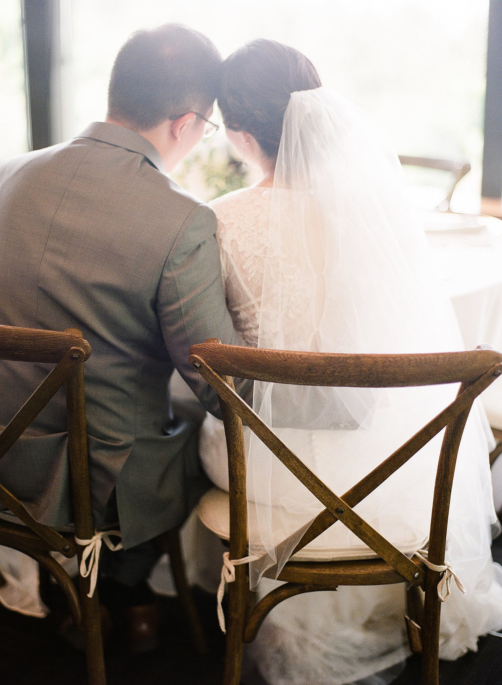 Bride-and-groom-on-vineyard-chairs-with-light