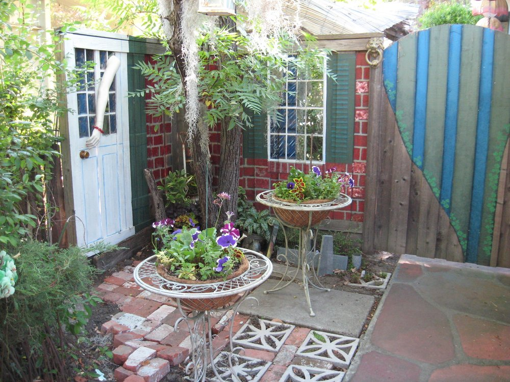 The gated entrance to the backyard of this homeowner's property was customized by painting the fence, gate and side of the stucco house to mimic a courtyard of one of his favorite hotels in New Orleans