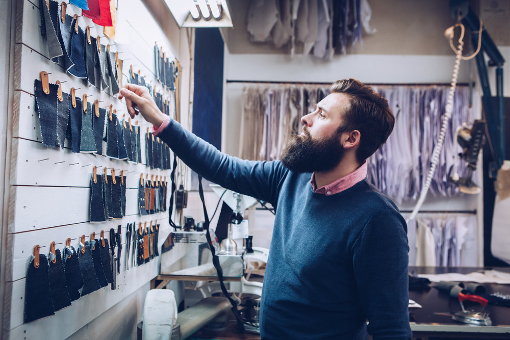 ©TomWoollard_Man-with-beard-choosing-custom-material-in-denim-manufacturers-workshop.jpg