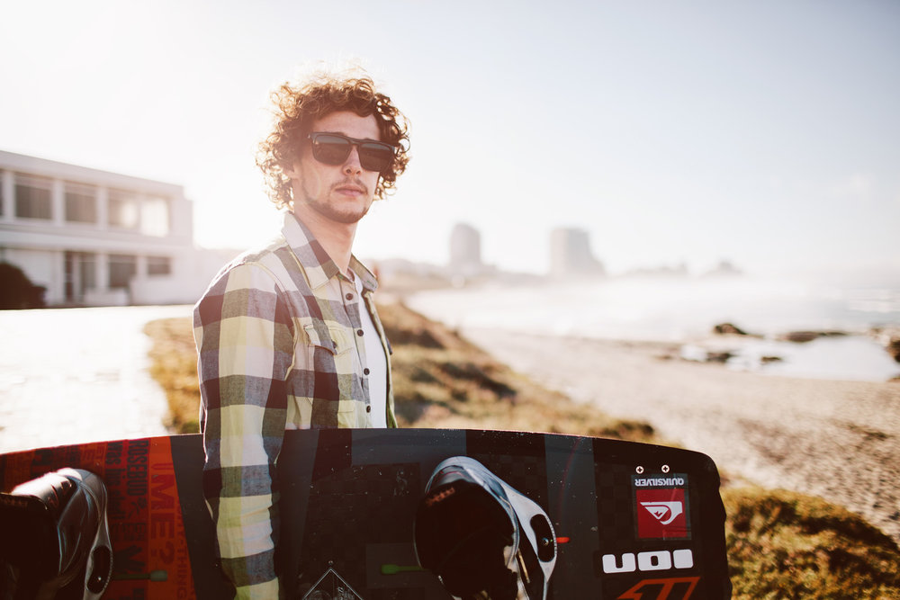 ©TomWoollard_Mario-Rodwald-kiteboarder-in-check-shirt-holding-kiteboard-on-beach-with-sunglasses.jpg