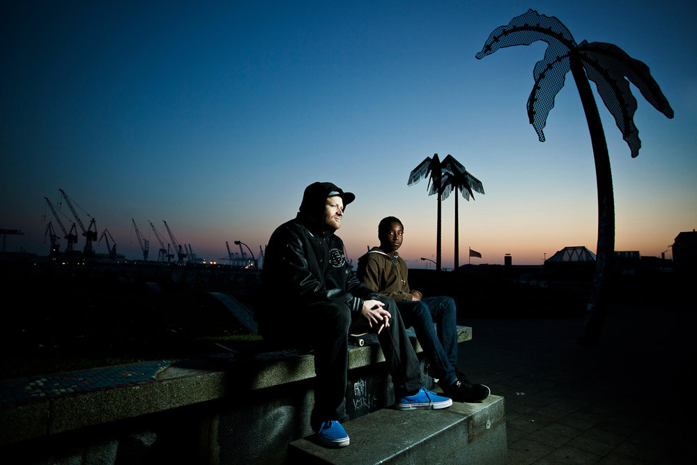 ©TomWoollard_Editorial-portrait-male-skaters-sitting-on-skateboards-at-hamburg-docks-evening.jpg