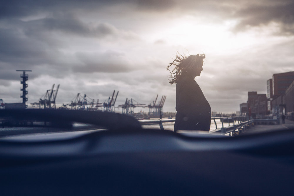 ©TomWoollard_Toyota_C-HR_road-trip-woman-silhouette-at-hamburg-docks-dramatic-sky-editorial.jpg