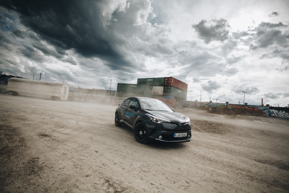 ©TomWoollard_Toyota_CHR_car-on-urban-dirt-wasteland-with-dramatic-clouds-sky-Munich-editorial.jpg