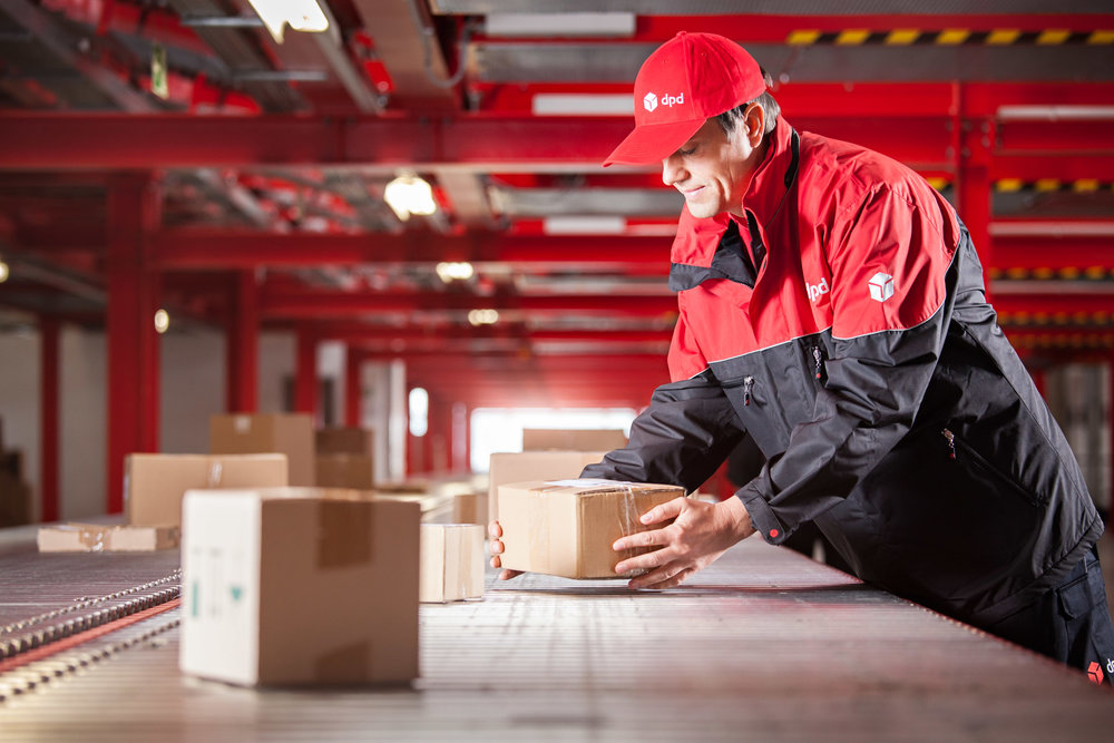 ©TomWoollard_DPD_Depot_Nuernberg-male-delivery-worker-places-parcel-on-conveyor-belt-with-care.jpg