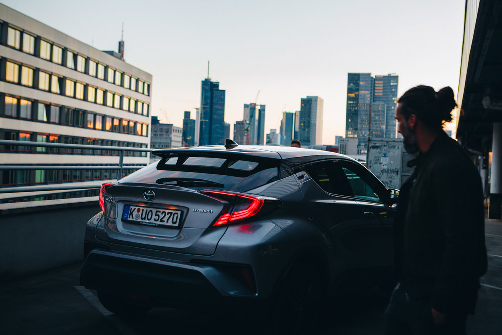 ©TomWoollard_Toyota_C-HR_car-editorial-lifestyle-urban-man-on-carpark-roof-Frankfurt-skyline-sunset.jpg