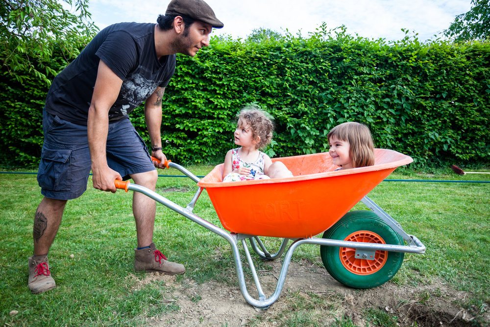 ©TomWoollard_OBI_editorial-lifestyle-father-with-young-daughters-playing-in-garden-wheelbarrow.jpg