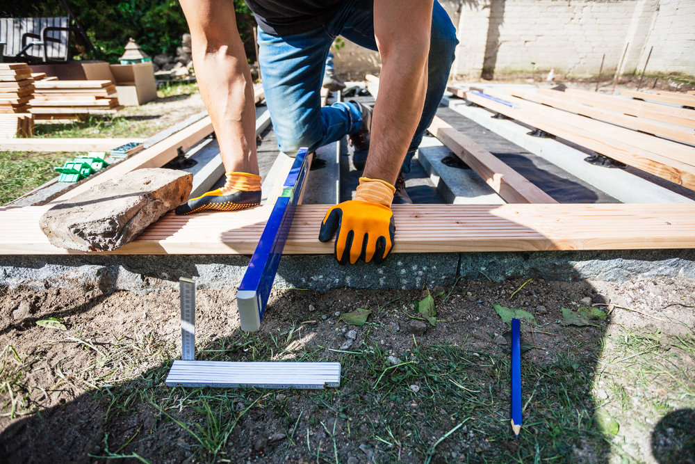 ©TomWoollard_OBI_Berlin-editorial-lifestyle-garden-construction-worker-building-wooden-terrace-measuring-tools.jpg