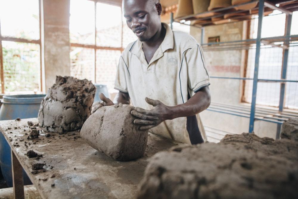 ©TomWoollard_Yunus-Social-Business_Uganda_Spoutsofwater-african-man-hand-moulding-clay-fllters-workshop.jpg