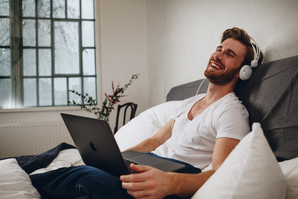 ©TomWoollard_NiveaMen_editorial-lifestyle-handsome-stylish-man-in-bed-laughing-headphones-on-laptop.jpg
