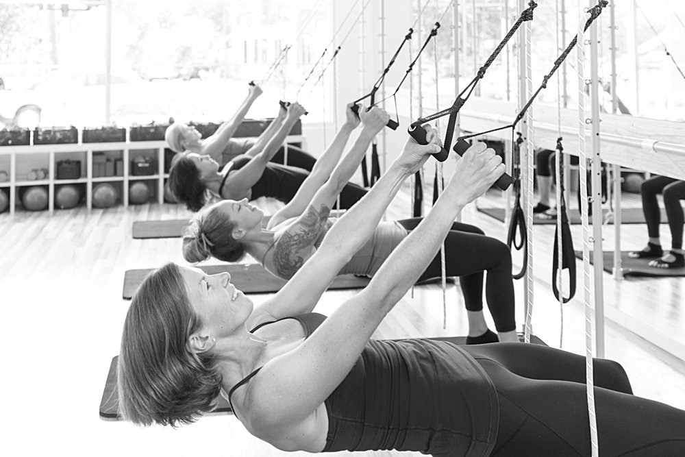 Cross Training - Bodhi is a simple and elegant suspension system, similar to TRX. This class is unique to The Pilates Barre as it includes the spring work from the Pilates protocol while the Tower also serves as an anchor for the ropes, handles and foot loops of the Bodhi system.  This class starts with a music driven cardio warm-up and moves into chest, shoulder, back, bicep and tricep work.  Standing leg work is done while holding onto the Bodhi handles, while planks, push-ups and side planks are performed while feet are suspended in Bodhi loops, both providing an added element of balance and challenge. Movement sequences include reaching limbs to the front, back or side of the body, moving the center of the body into an unstable lean, and pulling the weight of the body against the force of the ropes. The deep core is engaged throughout the class to stabilize the spine while challenging  the center of gravity for an amazing full body workout that creates amazing new levels of strength and flexibility!