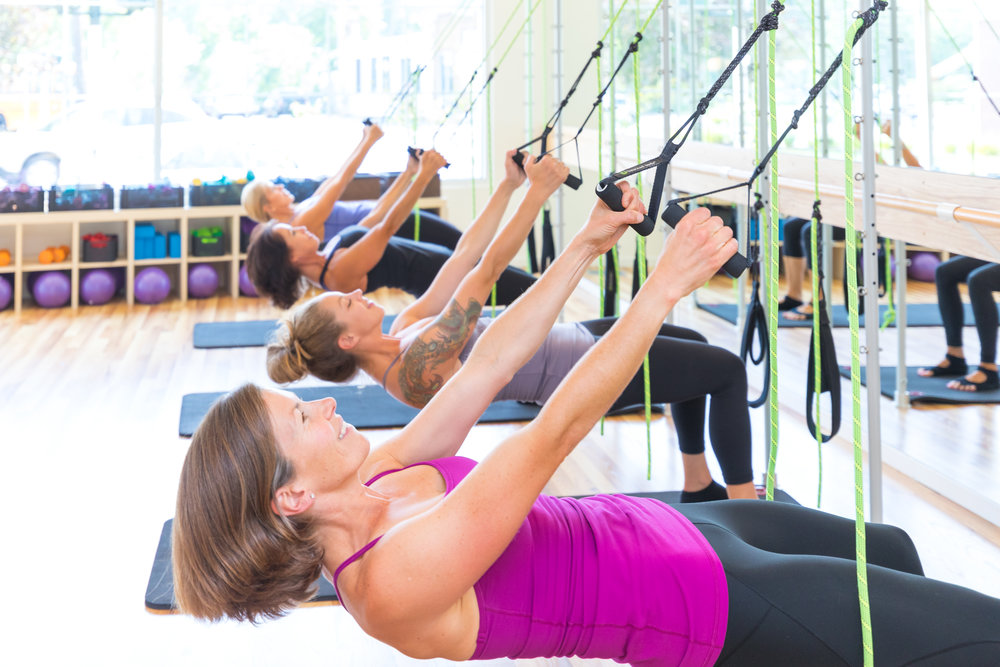 Unique -  to The Pilates Barre; we include the spring work from the Pilates Tower which serves as an anchor for the ropes, handles and foot loops of the Bodhi system.  Students get the benefit of TRX and Pilates in the same class which starts with a cardio warm-up and moves into chest, shoulder, back, bicep and triceps. Standing leg work is done while holding onto the Bodhi handles. Planks, push-ups and side planks are performed with feet suspended in the Bodhi loops, providing an added element of challenge.