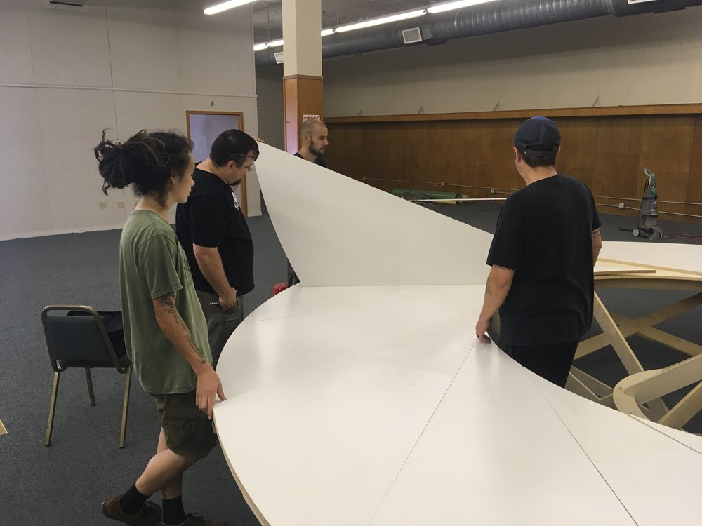 Volunteers placing the final pieces of the round table. The table is made of about 65 individual pieces and is CNC cut entirely out of plywood and melamine sheets.
