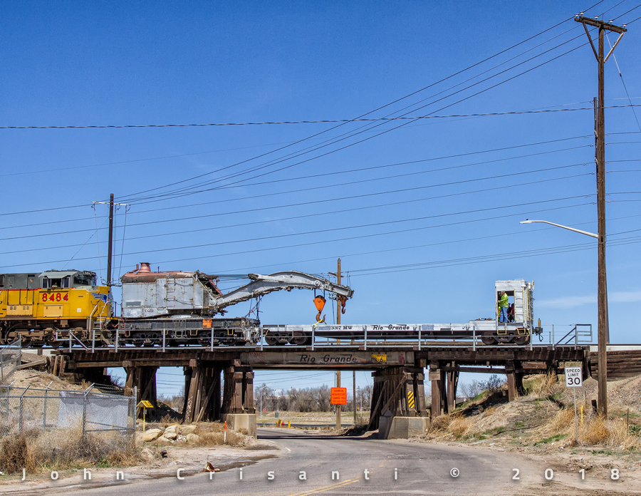 The steam crane and boom car have entered home rails for the last time as they cross over York Street on the Rio Grande lettered bridge on the Belt Line Connection in Denver.