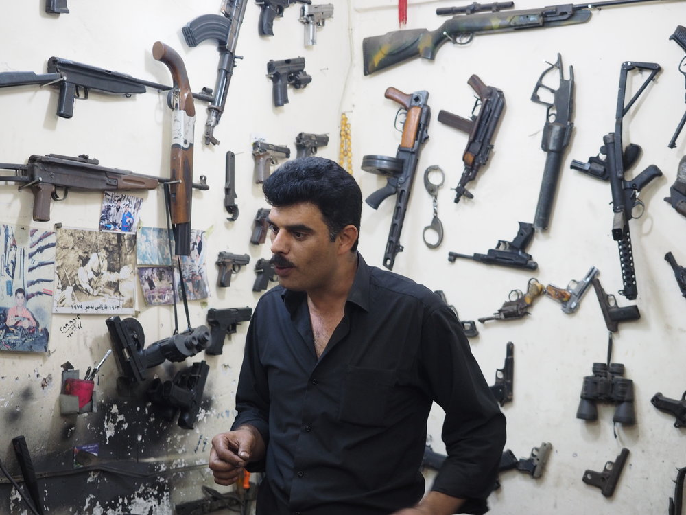 The gun shop. Note his wall of weapons includes handcuffs and an air rifle for those preferring non lethal solutions.