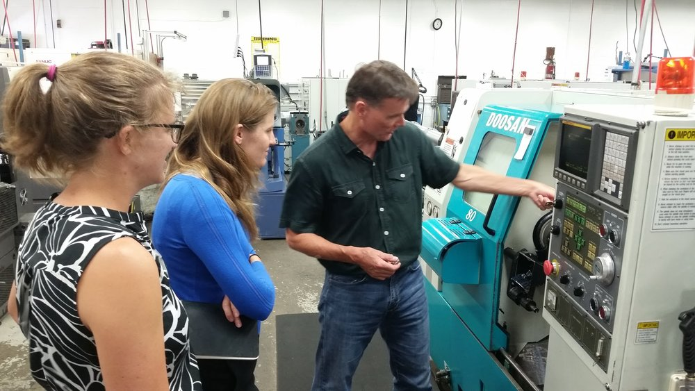 CIC Staffers Shellie Cohen (left) and Julia Hansen (center) watch CCG's Mark Flannigan (right) demonstrate on a milling machine.