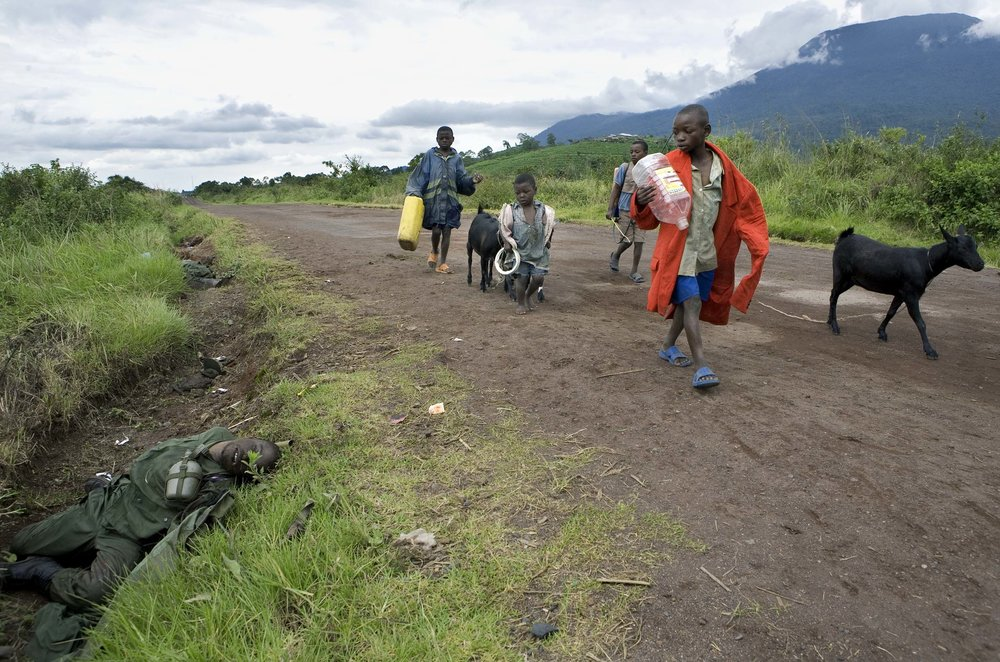 Displaced families walk past the body of a dead Congolese soldier, left on the road inside rebel controlled territory. Fighting escalated in recent weeks between the rebel group CNDP, the National Congress for the Defense of the People, and the Congolese army, displacing tens of thousands of people.