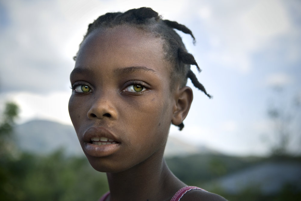 Jenny Duqai, 12, outside her home in Gros-Morne, Haiti.