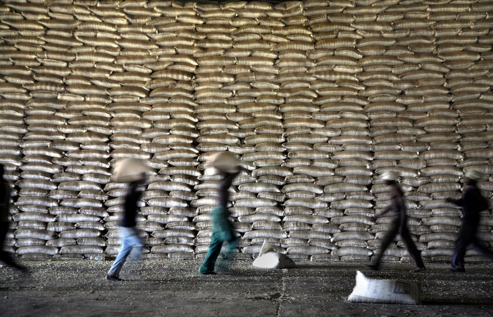 Workers carry sacks of maize to a train bound for Zimbabwe at the FRA, Food Reserve Agency, warehouse in Lusaka, the capital of Zambia.