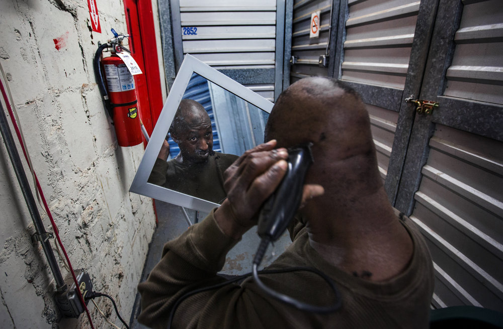 Michael Evans, 54, uses an electrical outlet to cut his hair in a hallway between storage units at Capital Self-Storage, October 14, 2015, in Washington, DC. Evans who has slept on the streets for years, stores his belongings at the facility, and spends much of his day around his unit. Many of the area homeless have possessions they want to keep safe, just nowhere permanent to live, so they store their belongings at Capital Self-Storage, where an upper-level unit costs $30/month. Some of the homeless patrons also spend their days in their storage units, when shelters are closed during midday hours. The storage facility near 3rd and Florida Avenue in Northeast, Washington, DC, is about to be replaced by a boutique hotel.