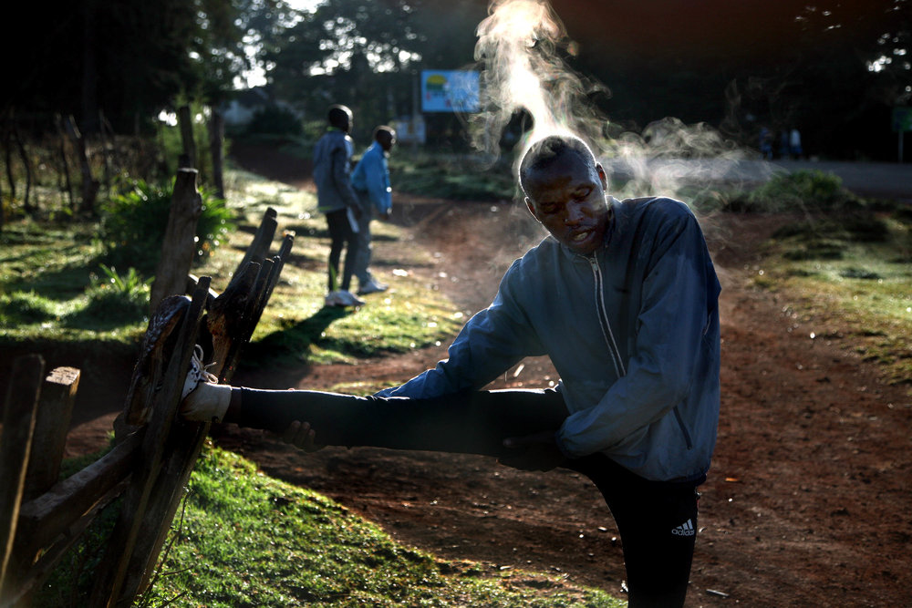 Steam pours off of a Kenyan runner as he stretches following his morning run at the high altitude training camp in Eldoret, Kenya. Elite runners from around the world come to the highlands of Kenya to train with the country's world class runners.