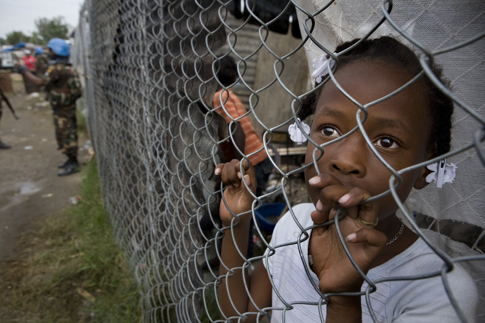 A young girl waits behind a fence for a food distribution at the stadium in Leogane where thousands of Hatians have sought refuge.