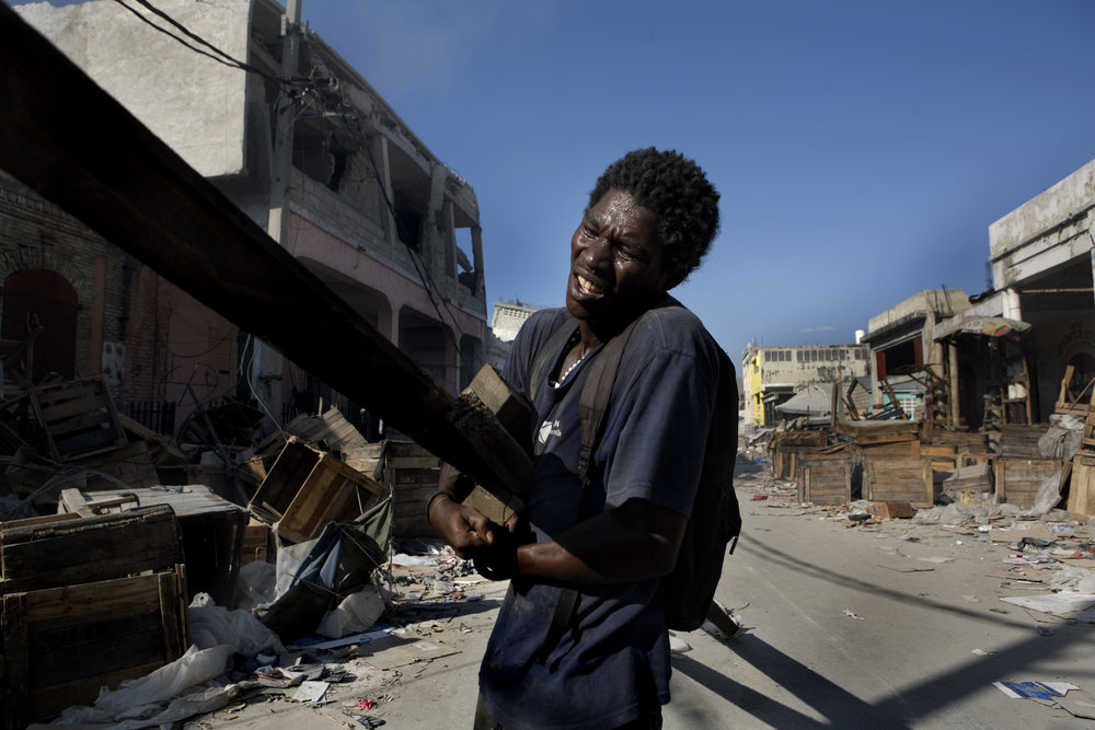 A Haitian man drags metal beams he salvaged through the central business district before American troops bulldoze destroyed buildings.