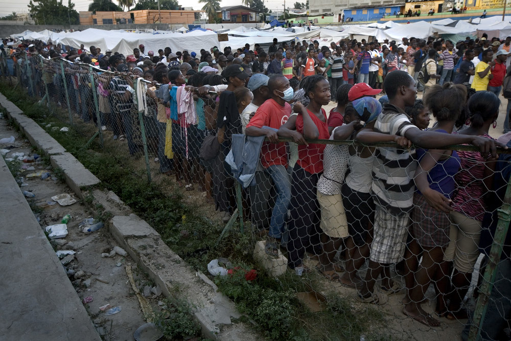 Thousands of displaced Haitians line up for a distribution of blankets and hygiene kits at a football stadium in Saint Terese. 2,133 people arevseeking shelter in the stadium.