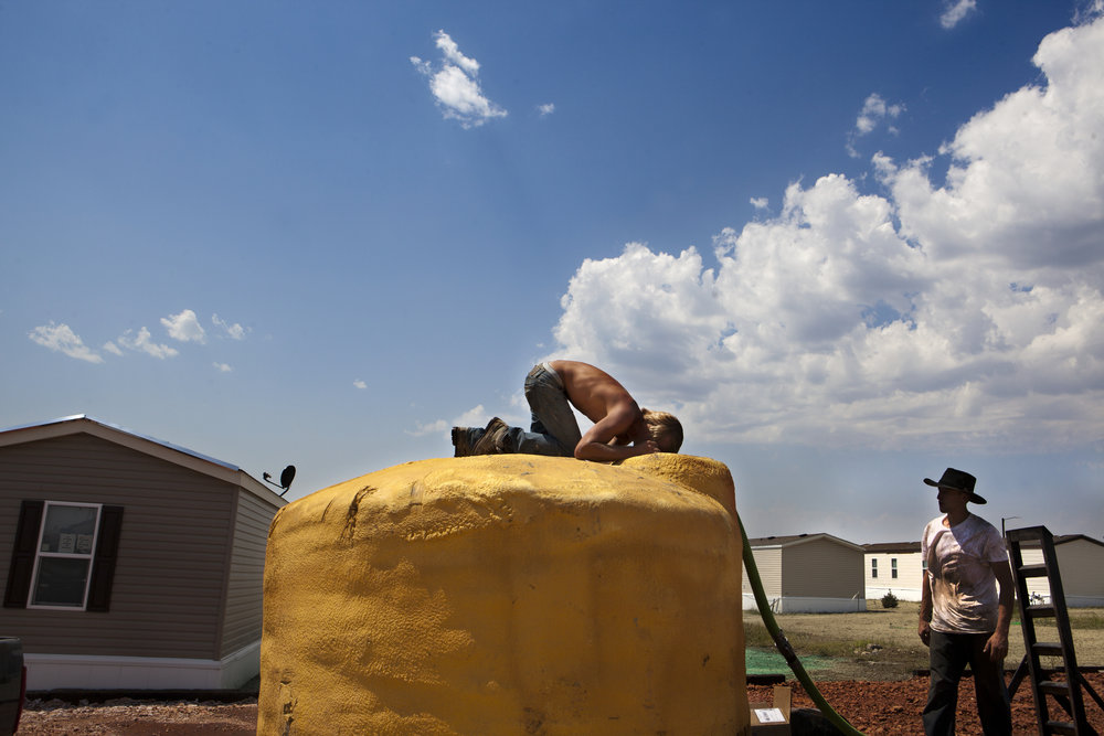 Young men who came to find work during the Bakken oil boom, construct temporary housing in Watford City, North Dakota.