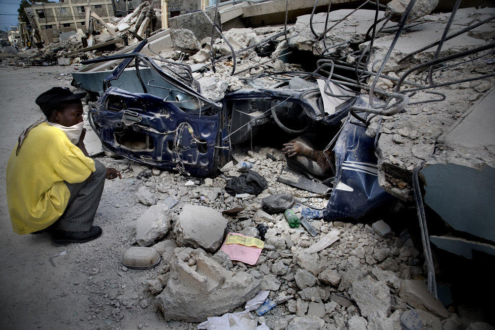 A woman's hand protrudes from her crushed vehicle, buried under a building in devastated Port-au-Prince.