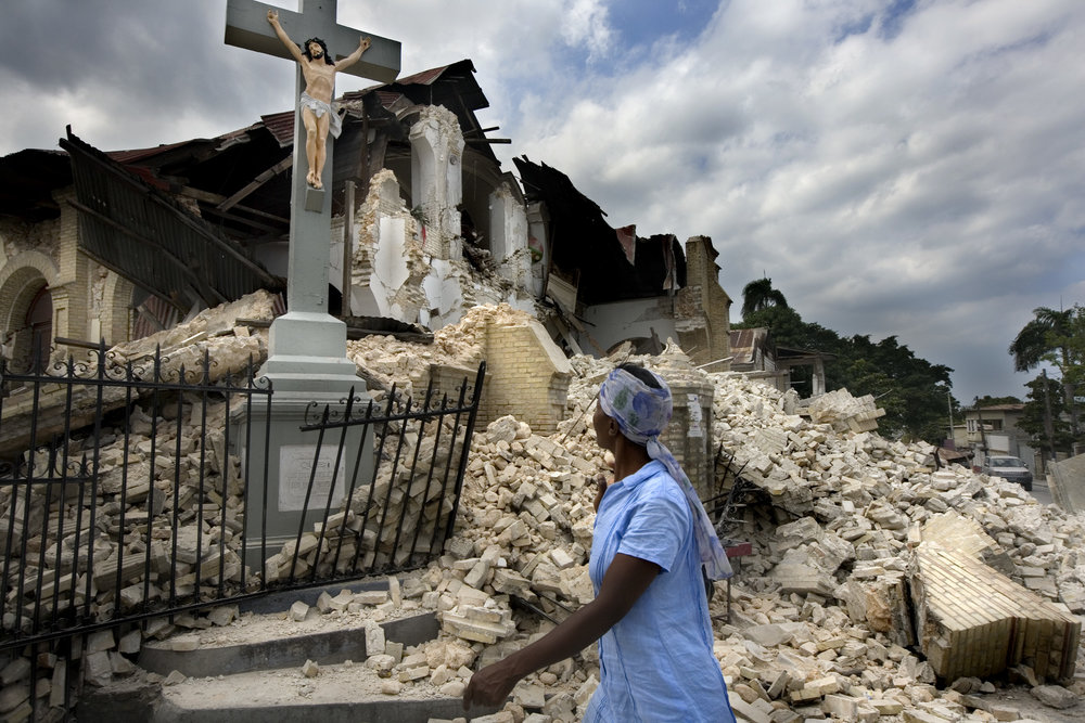 A woman walks by a destroyed church where only a statue of Jesus remains.