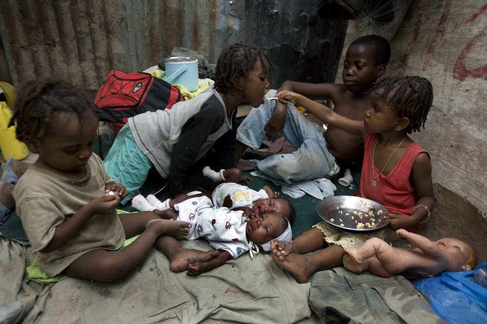 The six children of the Solie family, including one-month-old twins, eat in their shelter built on the median strip of a noisy, dusty road in Port-au-Prince.