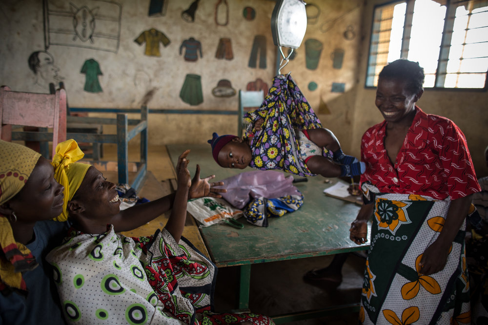 Mothers weigh their babies and have them vaccinated at an outreach health clinic set up in the tin-roofed classrooms at Ngamani Primary School in Kenya.