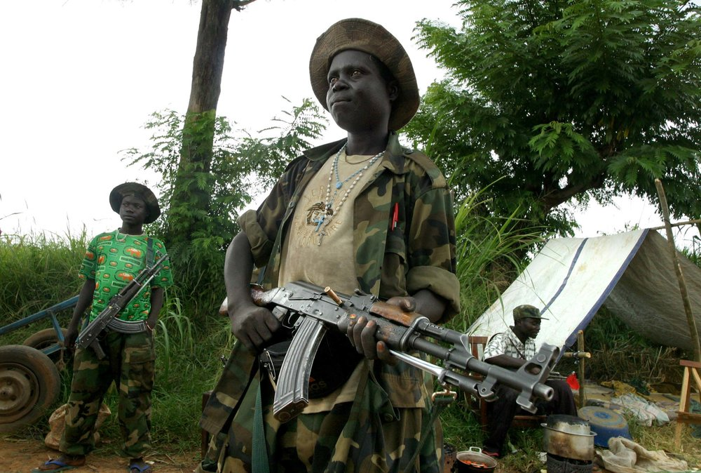 UPC child soldiers man a checkpoint on a road leading into the town of Bunia, northeastern Democratic Republic of Congo.