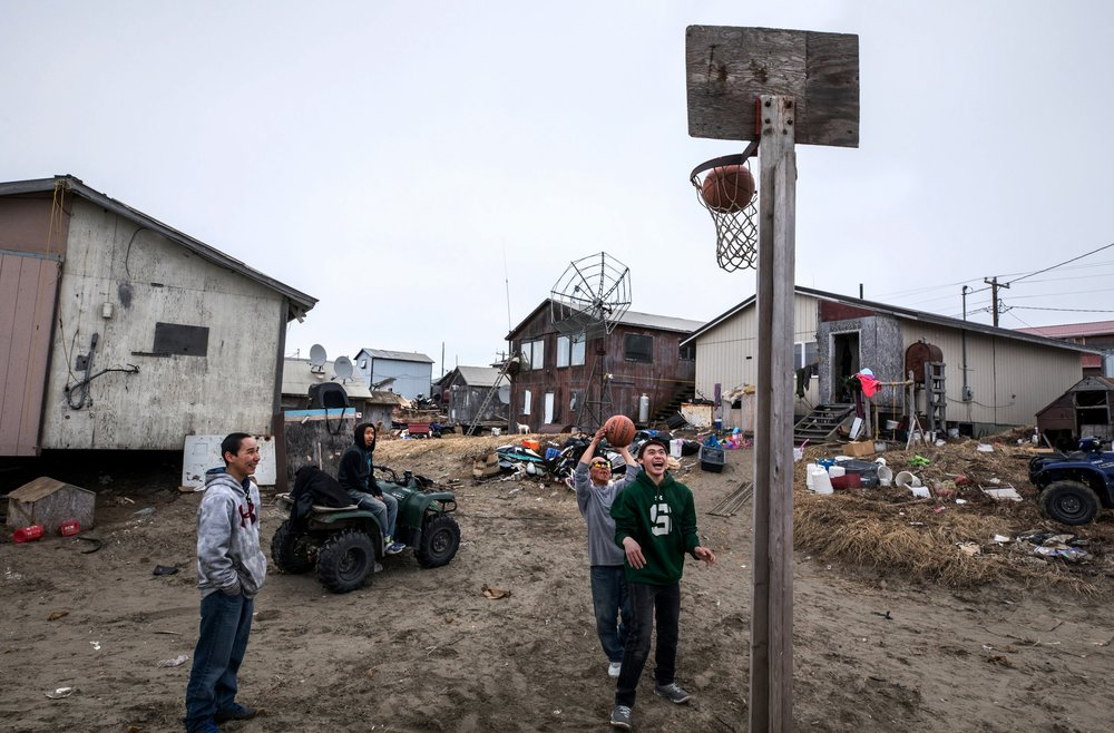 Young men play basketball in Shishmaref, Alaska, an Inupiat community of about 600 people near the Bering Strait. The residents of Shishmaref voted to relocate because their island is steadily disappearing from erosion and flooding due to climate change. Only one quarter mile wide and two and half miles long, Shishmaref has beengrappling with rising sea levels that have eroded more than 200 feet of the village. Climate change has resulted in a reduction in the sea ice which buffers Shishmaref from storm surges. The permafrost that the village is built on has also begun to melt, making the shore even more vulnerable to erosion. The Inupiat rely heavily on a subsistence lifestyle, hunting and gathering much of their food.