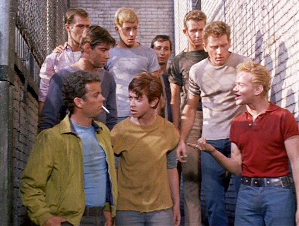 """Anybody's ist eine interessante Nebenfigur aus der Musical-Verfilmung  West Side Story  (1961), trotz des Namens, der auf """"Irgendwer"""" zurückgeht. Mitten in dem 50er-Jahre-Bandenkrieg zwischen den Jets und den Sharks kämpft Anybody's um Anerkennung, will auch Mitglied der Jets sein. Unklar bleibt, ob der Charakter kindlich sein soll, ein Kind, das für die Dauer der Prä-Adoleszenz als Tomboy herumläuft oder ob es sich um eine Transfigur handelt. Deutlich ist aber Anybody's Ehrgeiz, unbedingt dazuzugehören. Als körperlich kleinstes und schwächstes Glied wird sie von den älteren/größeren Jungs nicht ganz akzeptiert, teilweise gedisst. Anybody's ist ein typischer Mitläufer, der sich sehr anstrengt, sich zu beweisen. In neueren Aufführungen wird Anybody's zuweilen als Transjunge oder Butch-Lesbe inszeniert."""