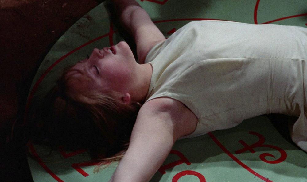Linda liegt auf dem Boden über ein magisches Symbol ausgestreckt, ihre Wangen sind rot, die Augen zu, der Mund auf. Halb zog es sie, halb sank sie hin - das Mädchen kann sich der sündigen Handlungen einfach nicht erwehren.