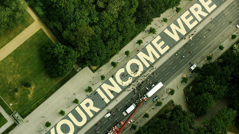 "Source: Medium; the phrase ""what would you do if your income were taken care of"" written on sidewalk."