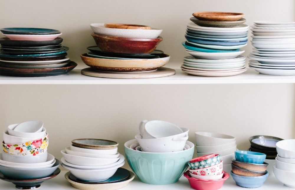 colorful bowls and plates on a white shelf