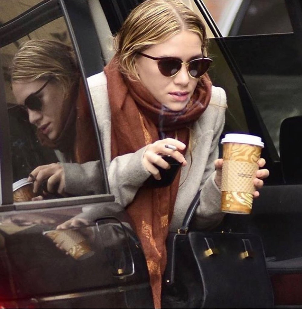 Mary-Kate exiting a black SUV in her signature look - which features a coffee in one hand and a half-smoked cigarette in the other.