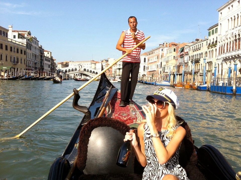 Travel Blogger Katy Johnson sips wine in the Grand Canal, Venice, Italy.